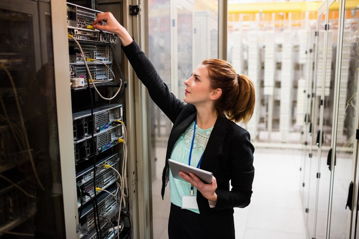 An engineer checks the cables of a data center server tower while holding a tablet in his left hand.