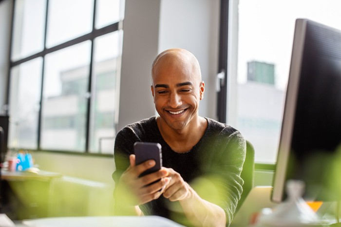 A person smiling while looking at their phone.