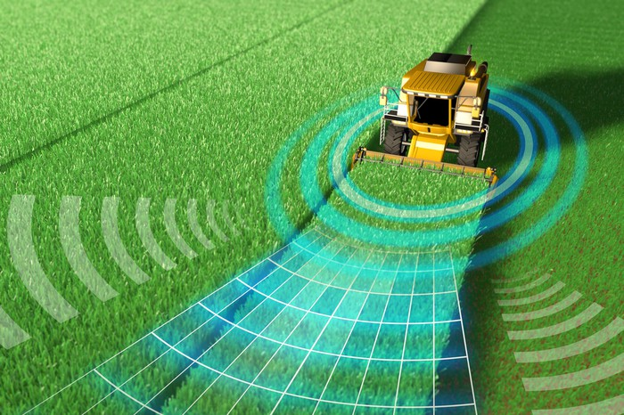 A harvester drives along a row in a field, harvesting a crop as imagery suggests that the harvester is sending out electronic signals to map its route using precision agriculture software.