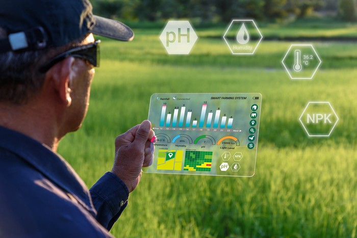 A farmer standing out in a field holds up a computer display with bar charts and fever lines showing on it and farming-related symbols float in midair in front of him.