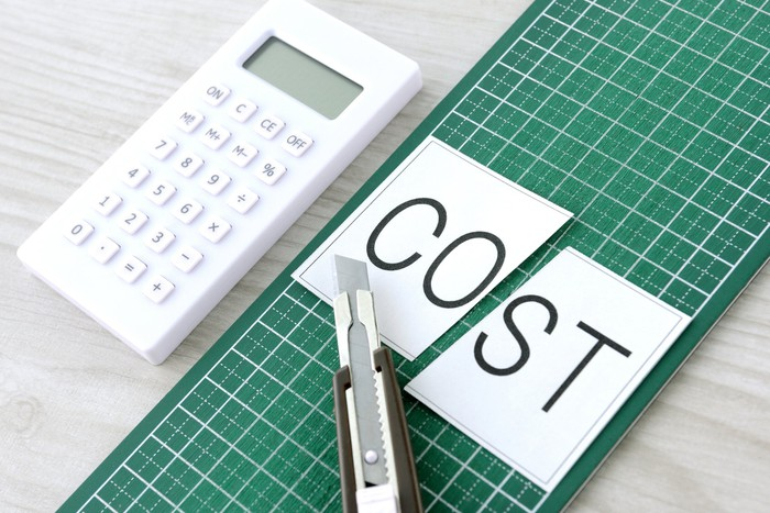 The word cost spelled out on a piece of paper split in half.