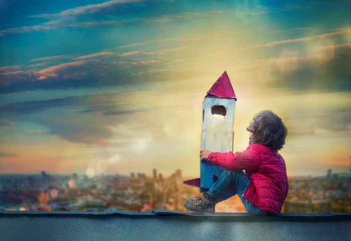 Smal child hugging a wooden toy rocket while sitting on a rooftop looking wistfully at the sky