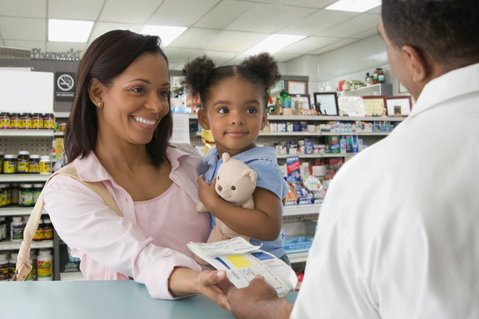 A smiling customer holds a child with a teddy bear at a pharmacy counter.