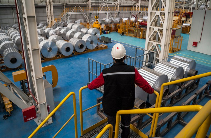 Worker wearing hard hat viewing factory floor with rolls of aluminum.