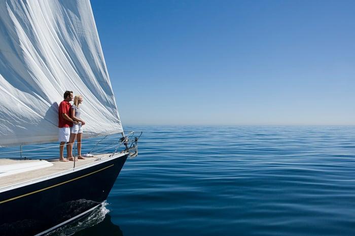 Couple debout sur le pont du magnifique yacht naviguant sur des eaux cristallines.
