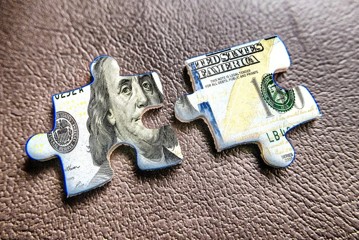 Two jigsaw puzzle pieces showing part of a $100 bill.