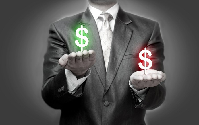 A person wearing a coat and tie holding palms out with a green dollar sign above one palm and a red dollar sign above the other palm.