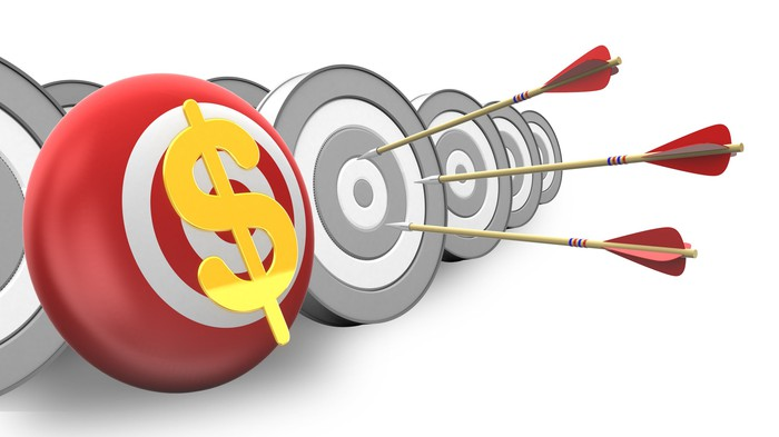 Multiple targets with three arrows stuck on one target next to a red and white target with a gold dollar sign on it.
