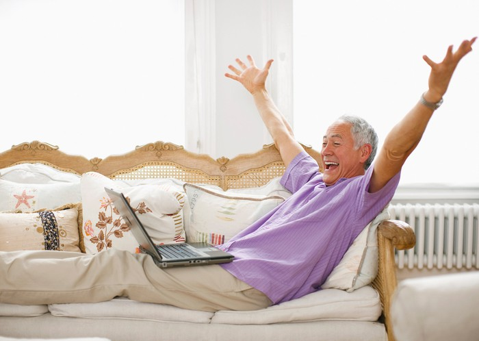 Smiling person lying on a sofa with hands in the air looking at a laptop.