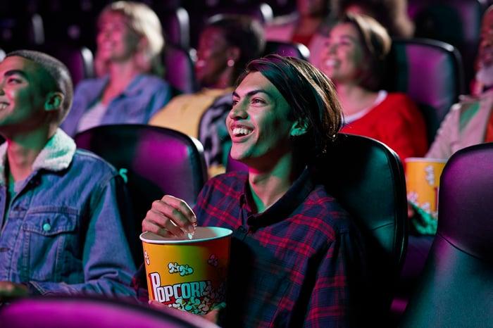Les gens mangent du pop-corn en regardant un film dans un cinéma bondé.