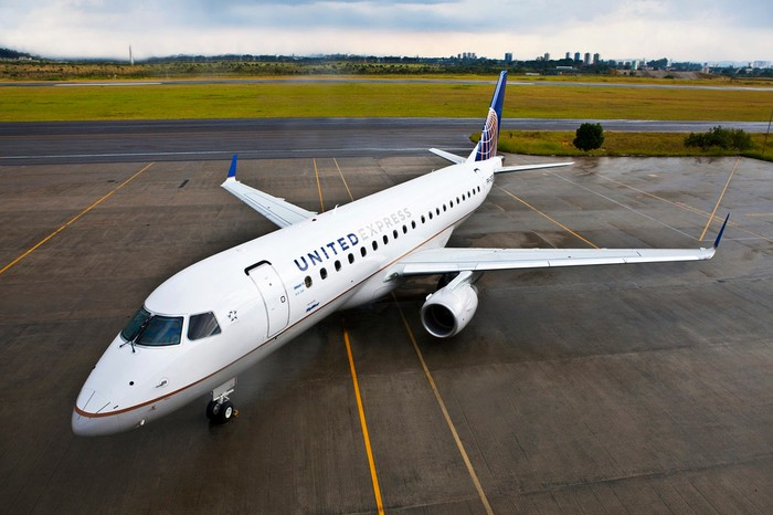 A United Airlines E175 regional jet parked on the tarmac.