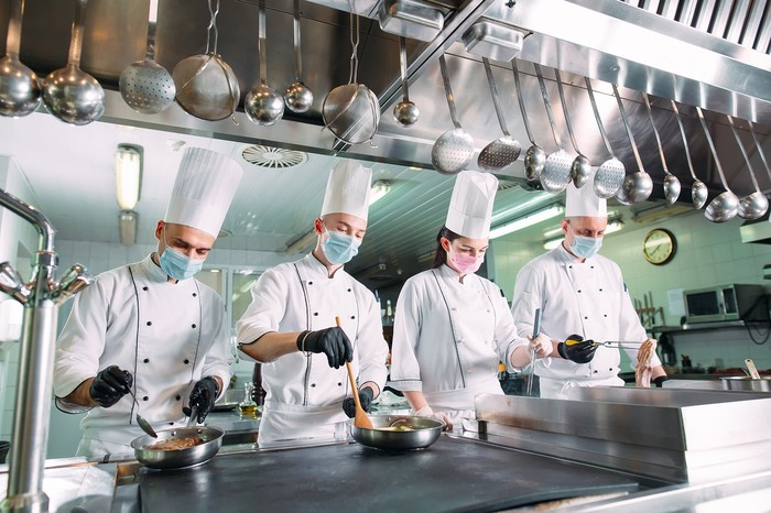 Hospitality workers in a kitchen.