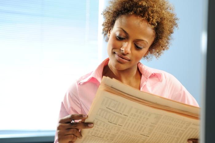 A businesswoman reading a financial newspaper.