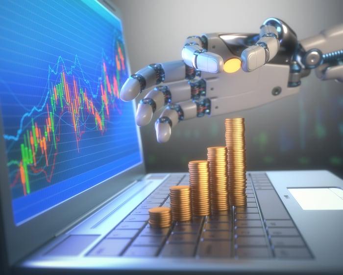 Une main robotique construit des piles de pièces montantes sur le clavier d'un ordinateur portable.