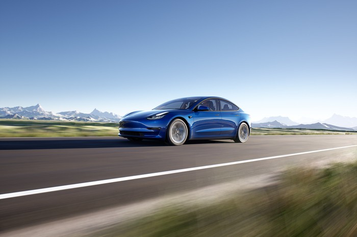 Blue Tesla Model 3 in motion on a sunny day.