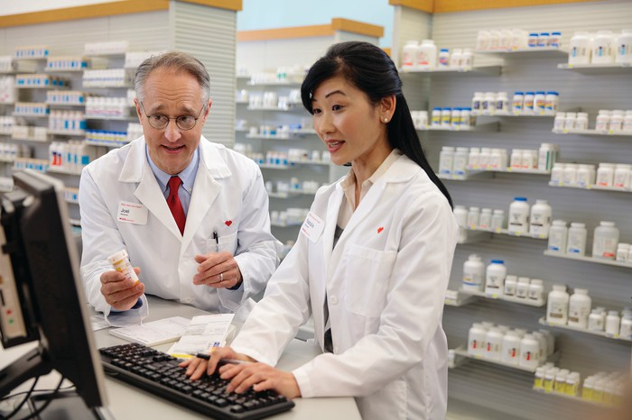 Two pharmacists collaborating while using a computer.