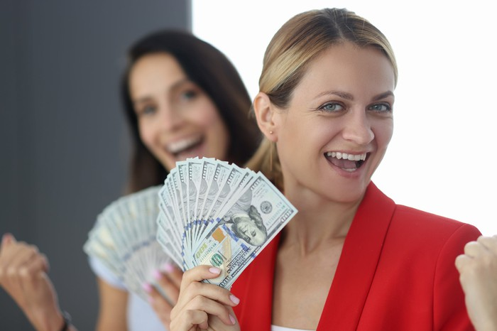 Two women holding cash that is fanned out.