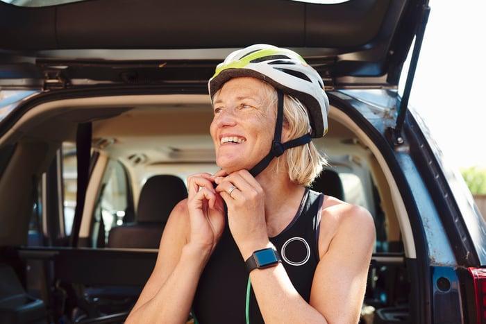 A woman wearing a smartwatch while preparing to go biking.