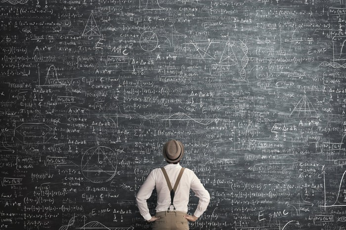 A person looks at a complicated math problem written on a very large blackboard.