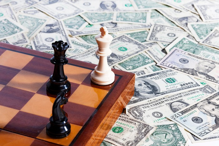 A chess board sitting on top of several dollar bills.