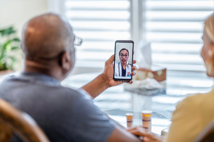 Two people look at a smartphone while consulting with a doctor via video chat.