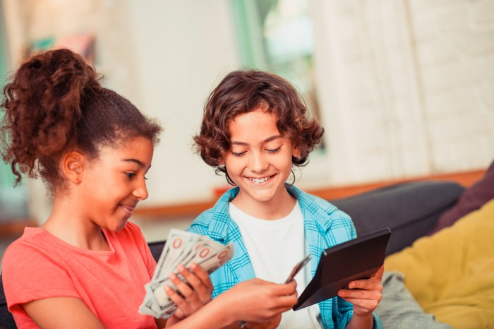 Two children holding cash and a calculator.
