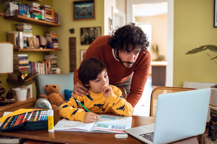 Child doing homework in front of computer as his father leans over him to help.