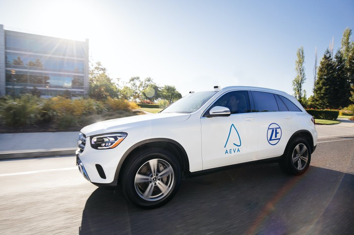 A white Mercedes-Benz SUV with visible lidar sensors and Aeva and ZF logos on its doors.