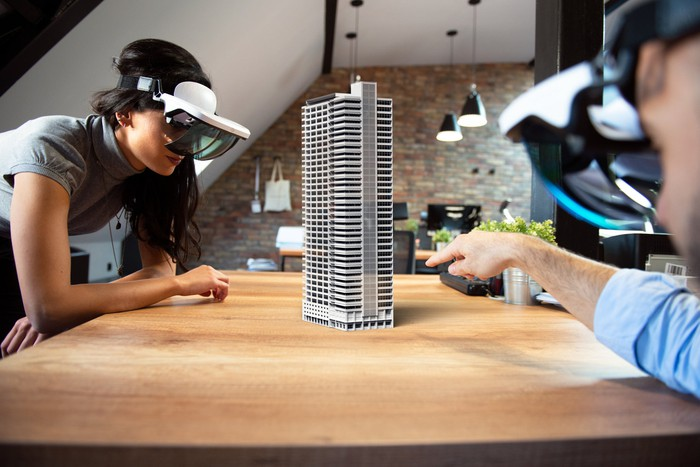 Architects viewing a building model using augmented reality goggles.