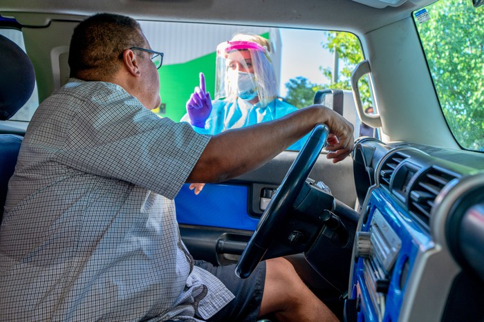 A person in a drive-up COVID testing station.