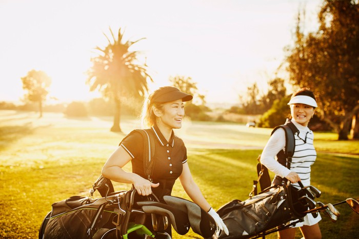 Two smiling people carrying golf club bags on golf course.