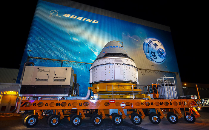 Boeing's Starliner space capsule on a trailer in front of Boeing space image.