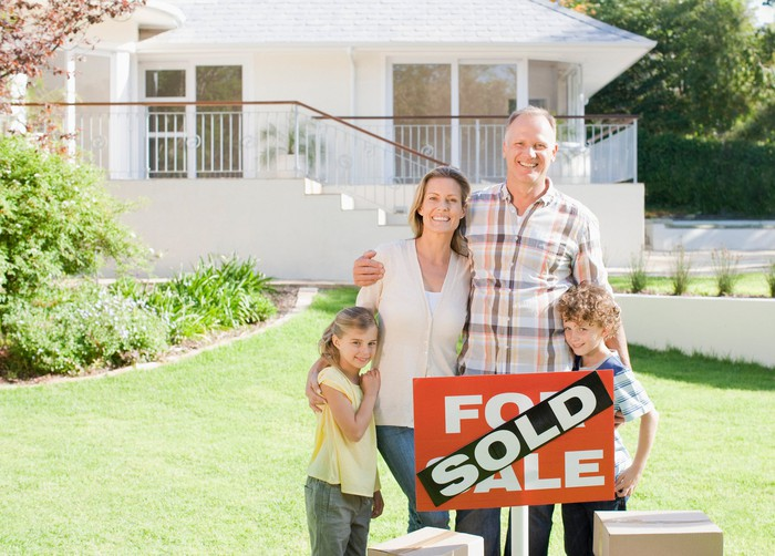 Family standing in front of a sold home.
