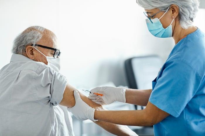 A nurse giving an older person a vaccine jab.