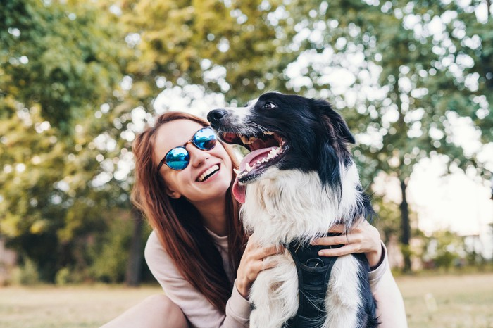 A happy woman in sunglasses with her dog outside.