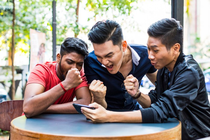 Three men celebrating while looking at a phone.