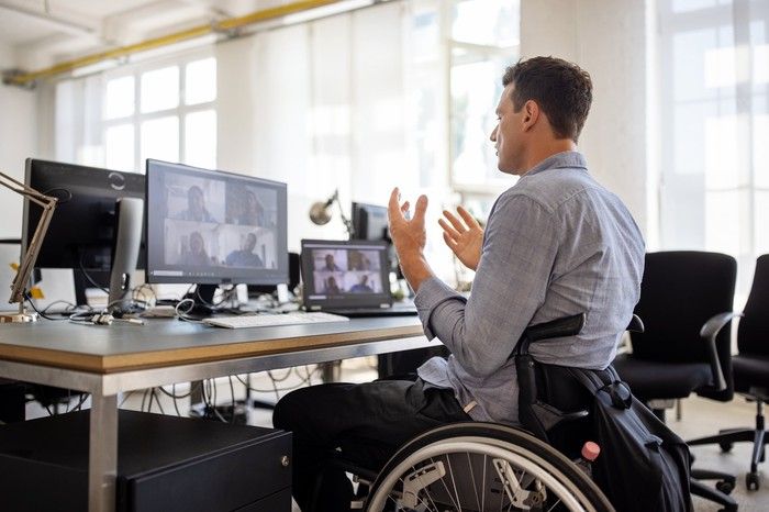 Someone using a wheelchair in front of a computer displaying a video conference.