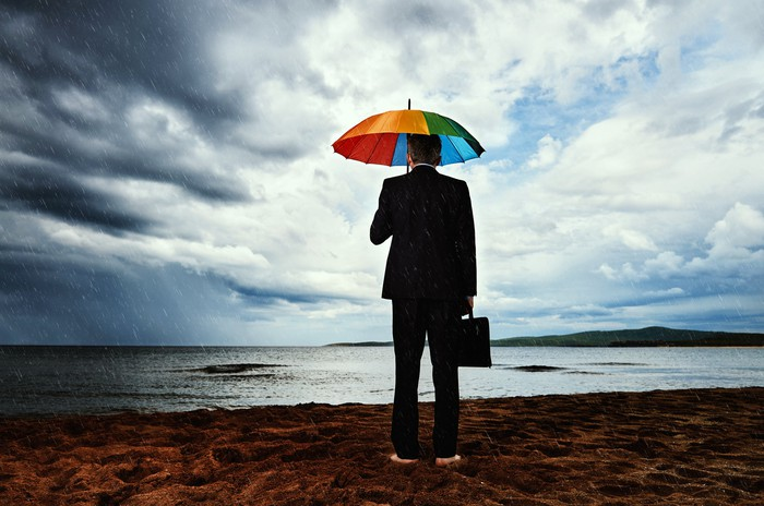 Businessperson standing in front of lake barefoot and holding umbrella as storm clouds gather in the distance.