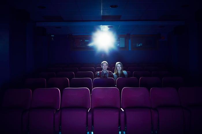 Deux personnes assises dans une salle de cinéma vide.