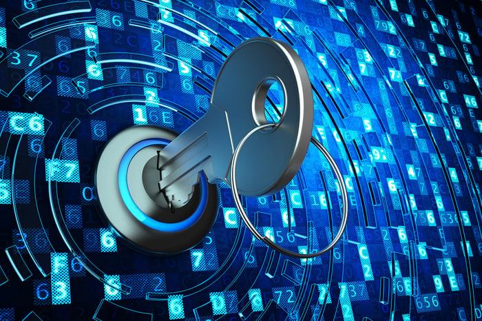 Une clé placée dans une serrure, avec des dizaines de codes alphanumériques entourant la serrure.