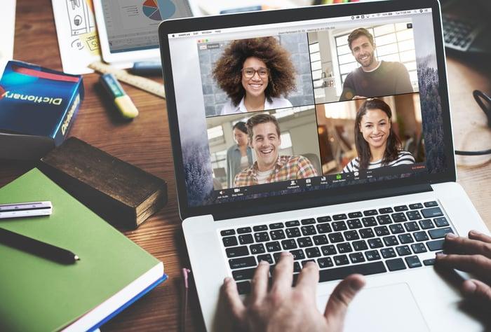 Une personne utilisant un ordinateur portable pour mener une conférence Web avec quatre autres personnes.