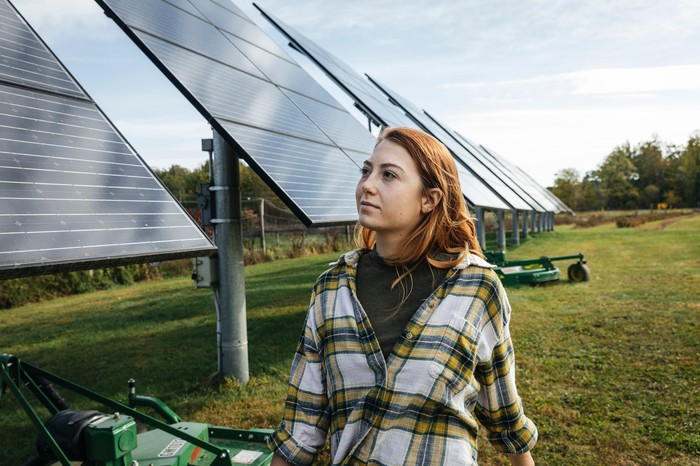A person looking at solar panels on a farm.