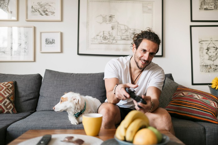 Young person sits on the couch at home beside a dog while playing video games.