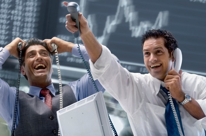 Excited stock brokers talk on the phone with clients as a stock jumps higher.
