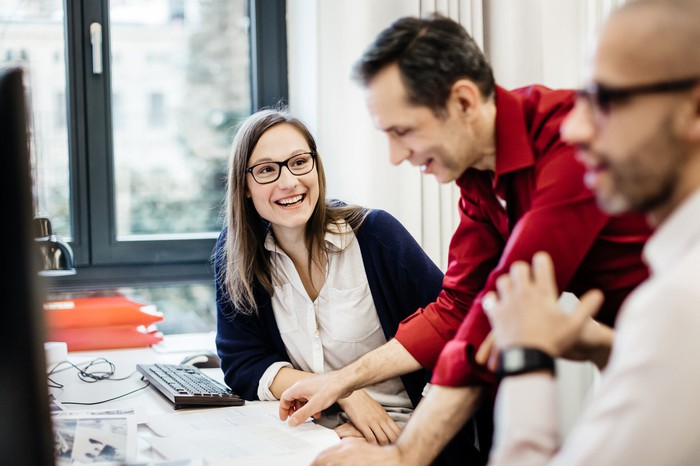 Businesswoman sitting on work desk and smiling, while a colleague explains something. There is also another colleague besides the woman.