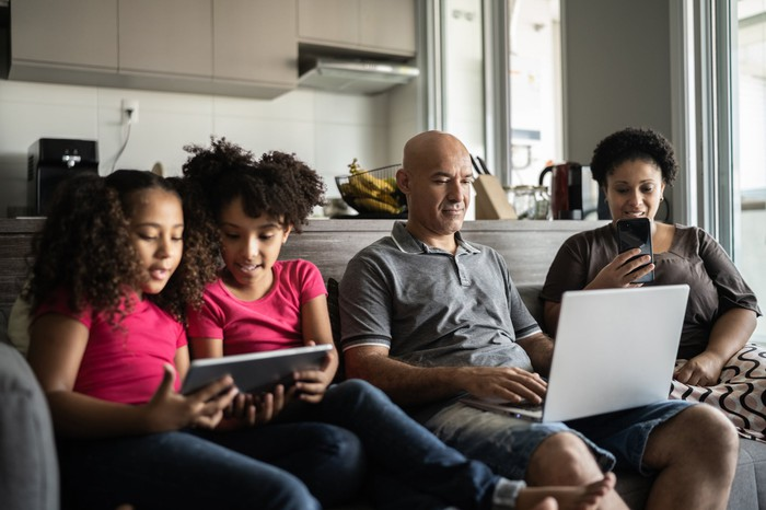 Une famille est assise sur un canapé pendant que le père travaille sur son ordinateur portable, la mère regarde son téléphone et les deux enfants partagent une tablette.