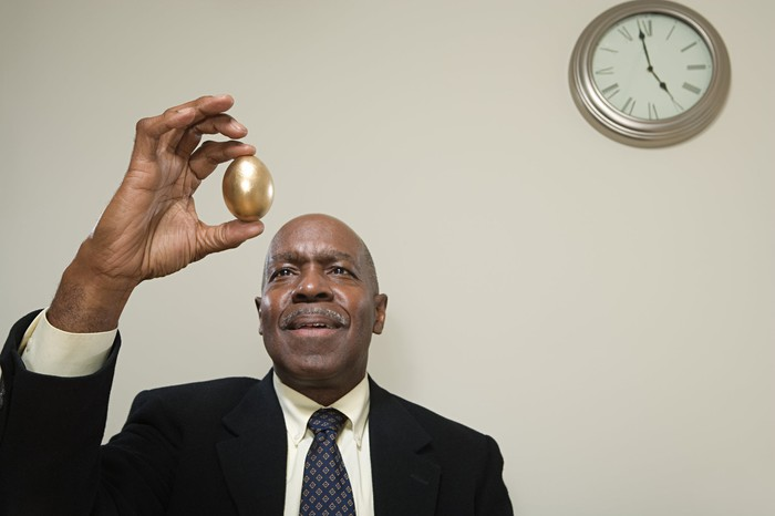 A man in a suit holding up a golden egg with a clock on the wall behind him.