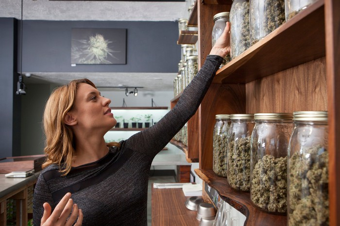 A shopkeeper reaches for a jar of cannabis on the shelf in her dispensary.