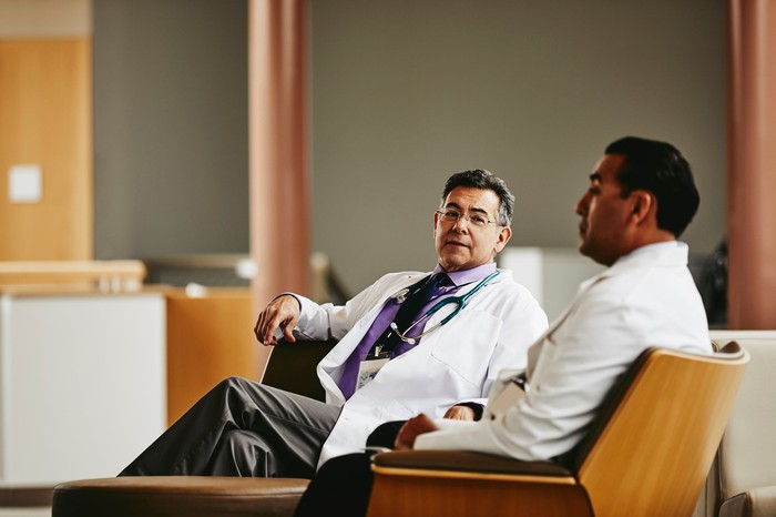 Two doctors chat while sitting in a hospital waiting room.