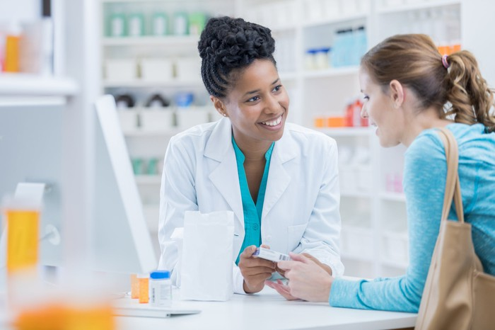 Pharmacy technician discussing product with a customer.